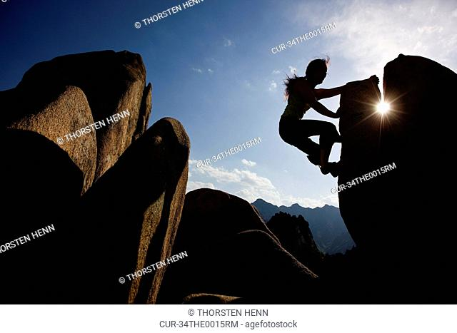 Silhouette of woman climbing rocks