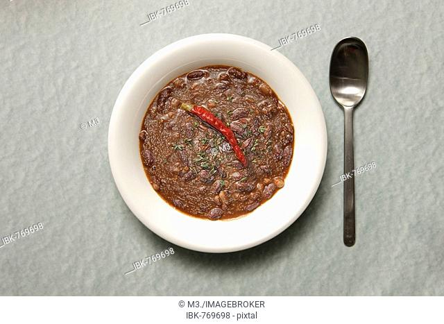 Spoon beside a plate of stale chili con carne