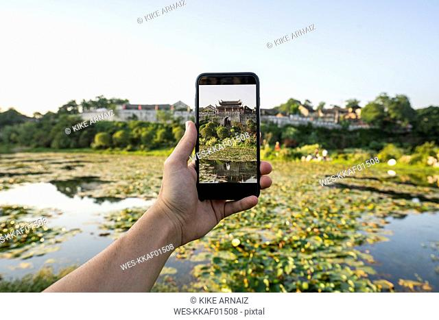 China, Qinyang, man holding smartphone, picture