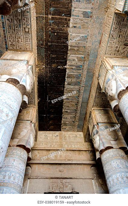 Ancient Egyptian hieroglyphs and carved paintings on the ceiling and columns, partially restored, of the Temple of Hathor in Dendera, Egypt
