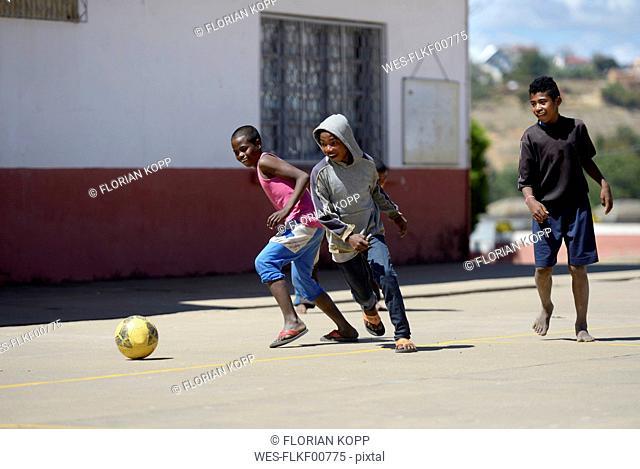 Madagascar, Fianarantsoa, Boy playing soccer in school yard
