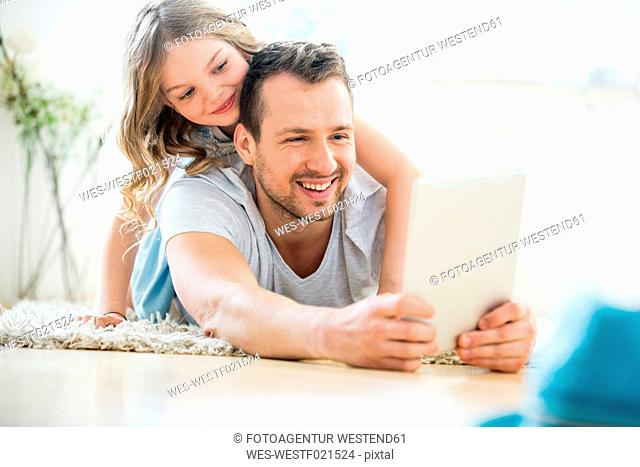 Father and daughter lying on floor, using digital tablet