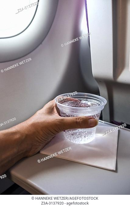 Hand holding a plastic cup with sparkling water inside an airplane