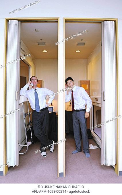 Businessmen standing in capsule hotel
