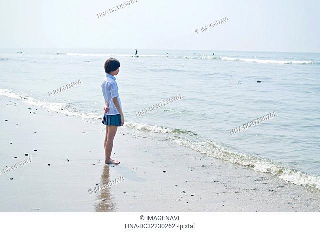 Female teenage student in uniform standing at beach