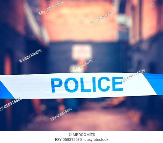 British Police Tape Around A Crime Scene In A Grungy Urban Alley