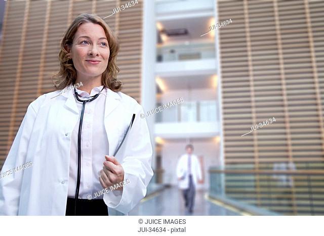 Portrait of confident doctor wearing lab coat in hospital corridor