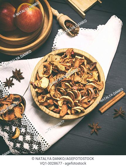 dried apple slices in a brown wooden bowl on a black wooden table, top view, vintage toning