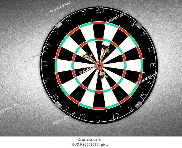 A dartboard with three darts in bullseye