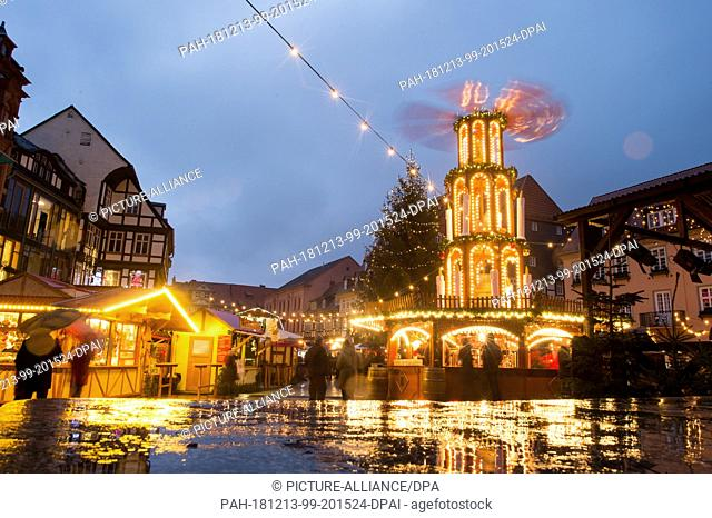 12 December 2018, Saxony-Anhalt, Quedlinburg: Christmas tree and rotating tree stand on the Christmas market, whose stalls are reflected in the wet stone of a...