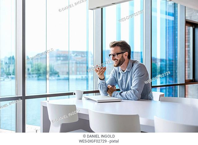 Smiling man using cell phone in modern office