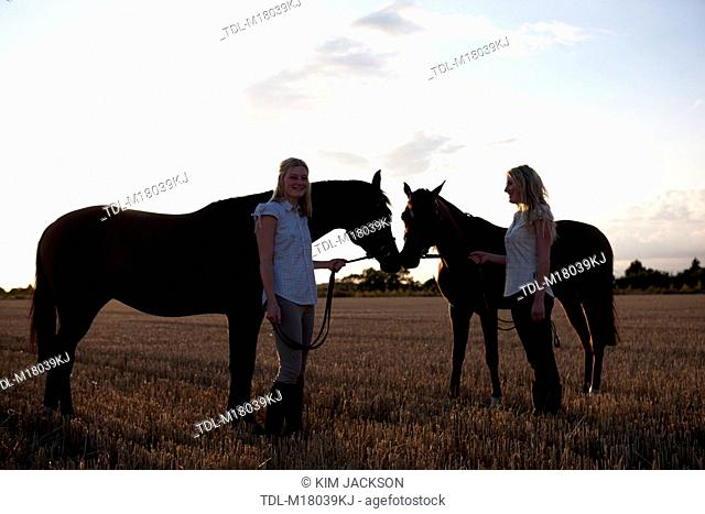 Two young woman holding Arabian horses