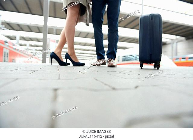 Low section of business couple on railway platform, Munich, Bavaria, Germany, Europe