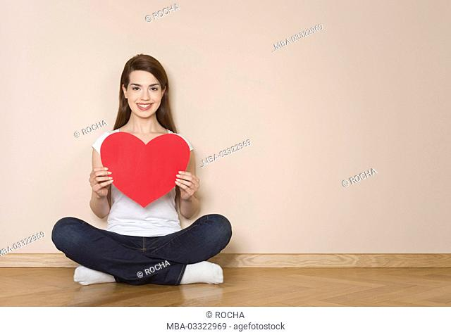 Woman holds big red heart in her hands, happy, smile