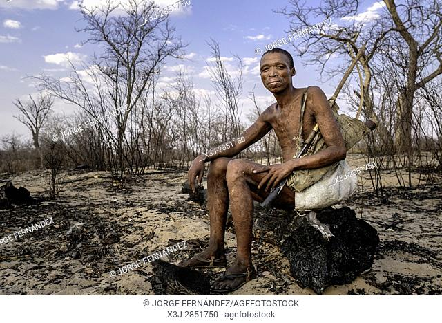 Portrait of Mr. Cqunta sitting down on a burned log with bow and arrow wearing his traditional attires to entertain the tourists