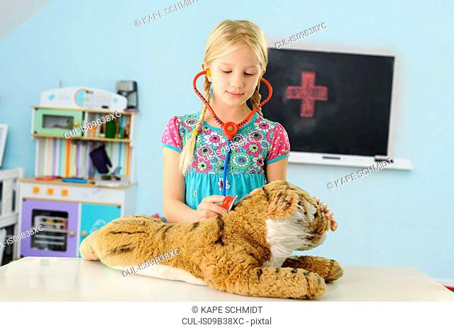 Girl pretending to be vet examining toy tiger using stethoscope