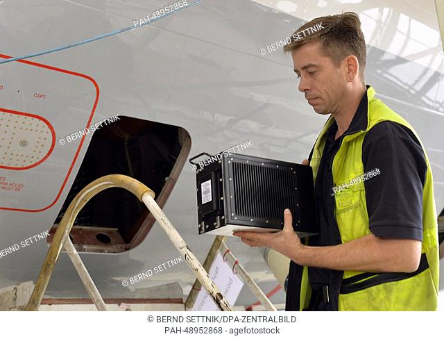 Lufthansa technician Andreas Behnecke carries the server for the new entertainment system to an Airbus aircraft at the Lufthansa hangar in Schoenefeld, Germany