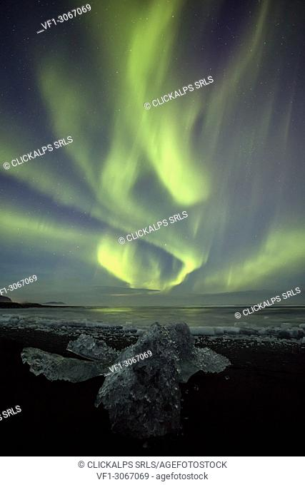 Northen Lights over block of ice in Jokulsarlon Glacier Lagoon, Austurland, Eastern Iceland, Iceland, Europe