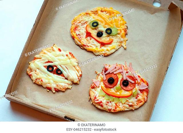 Halloween pizza with monsters, above scene with decor on a craft paper box background, idea for home party food, easy, healthy and delicious fun food party...