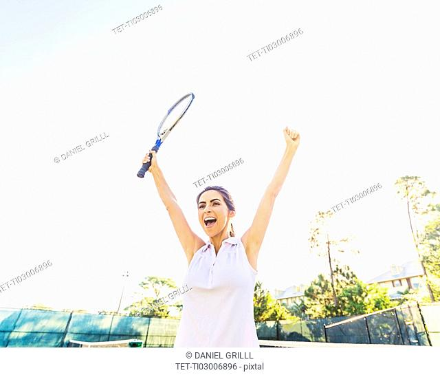 Portrait of young woman holding tennis racket, raising arms in celebration