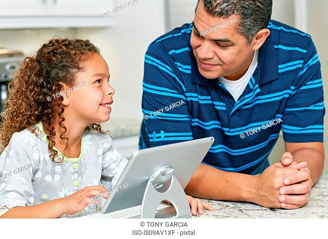 Father and daughter using digital tablet face to face smiling