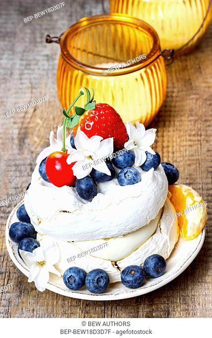 Meringue cake decorated with fresh fruits, standing on wooden table