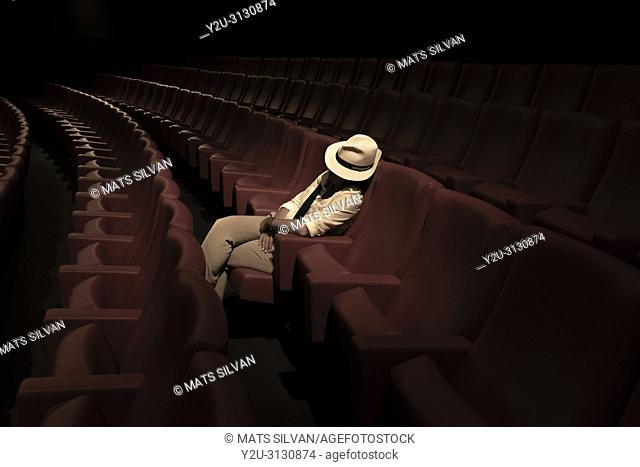 Woman with Hat Sleeping Alone in Movie Theater
