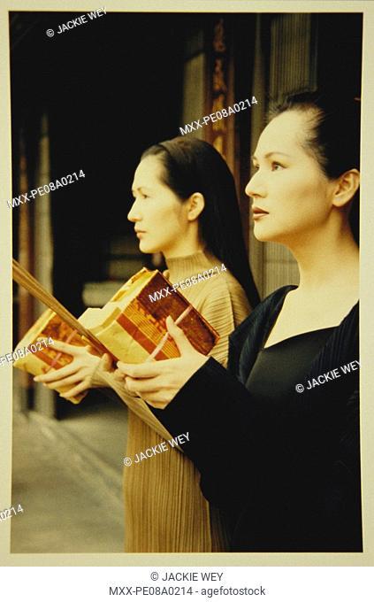 Asian women holding books