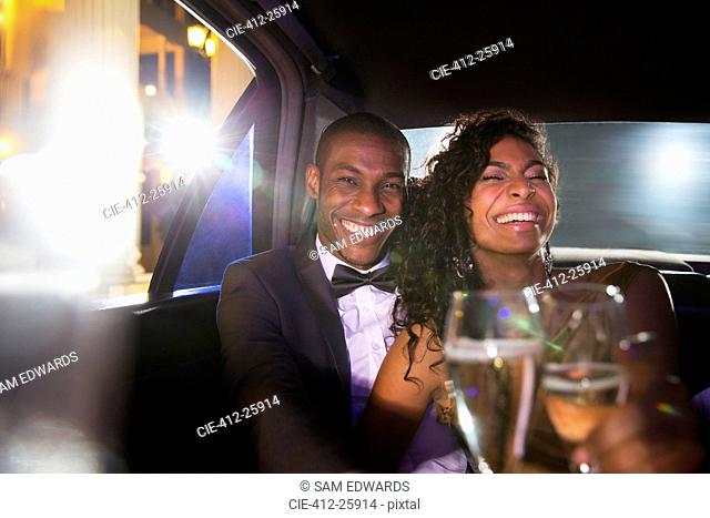 Laughing celebrity couple drinking champagne inside limousine at red carpet event