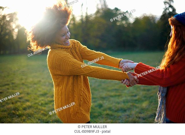 Two young women, in rural setting, holding hands, fooling around