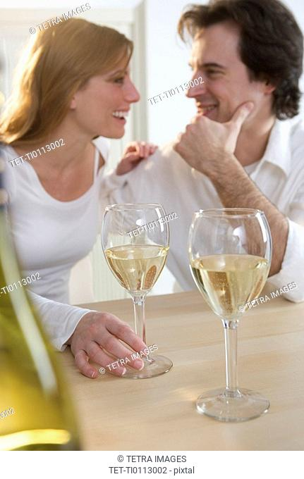Laughing couple with white wine