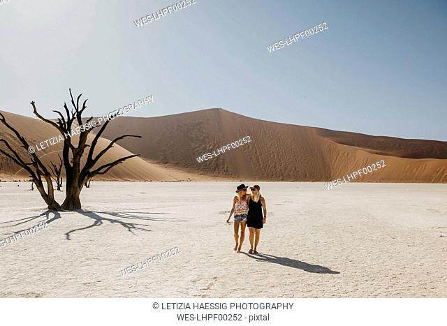 Namibia, Namib desert, Namib-Naukluft National Park, Sossusvlei, two girlfriends walking in Deadvlei