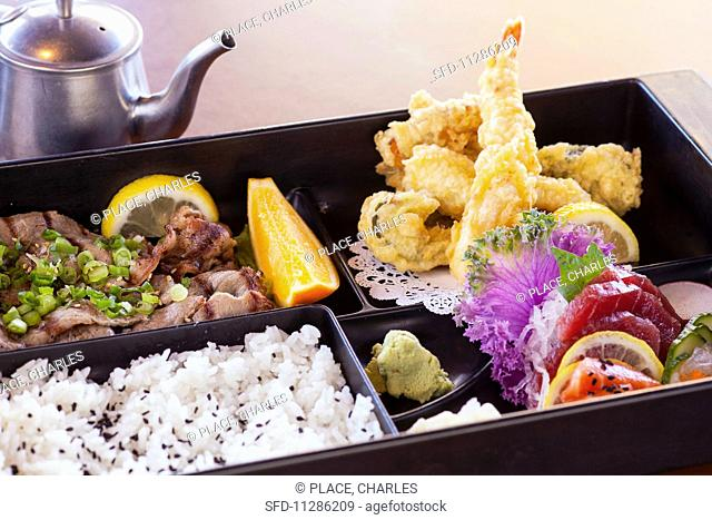 A Bento box with Amiyaki beef, shrimp and vegetable tempura, sashimi and rice (japan)