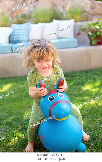 Caucasian baby boy playing with toy in backyard