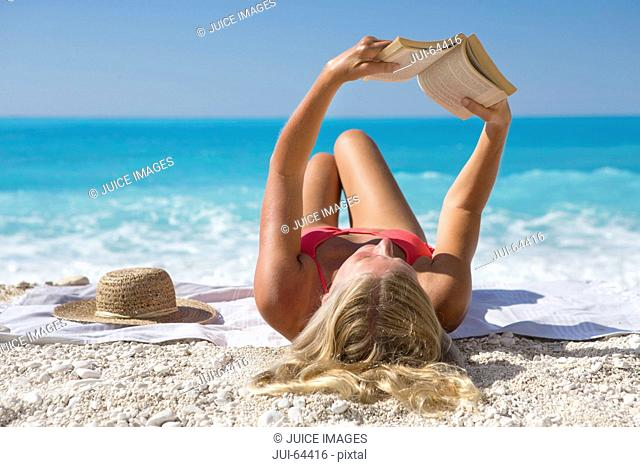 woman, reading book, lying on towel on sunny beach