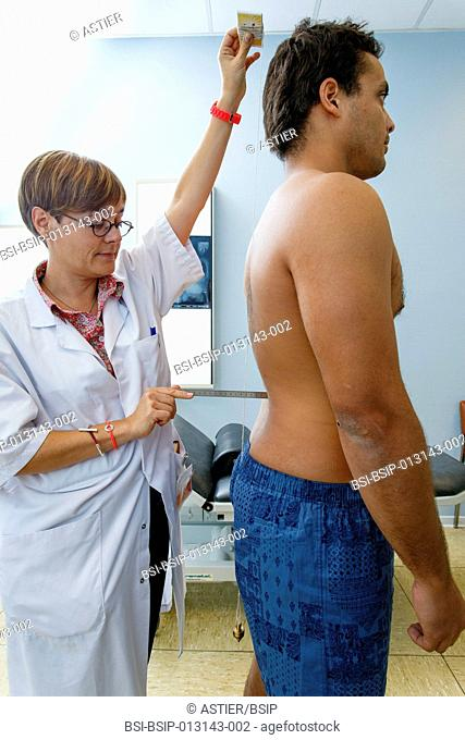 Clinical research in the GHICL. Physical medicine unit in Saint Philibert hospital in Lille, France. Clinical exam, the doctor looks for signs of scoliosis in...