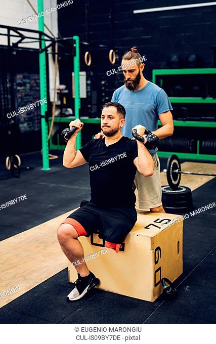 Man with disability using kettlebells with trainer