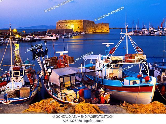 Cretan boat moored Heraklion harbour and Venetian fortress Koules Castle, Iraklio, Crete, Greece