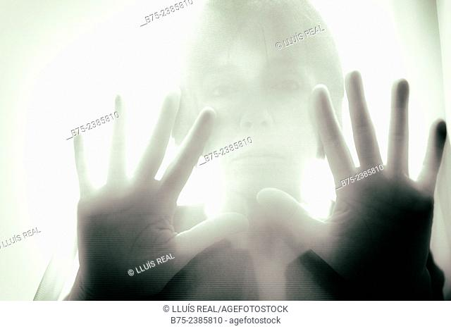 Closeup of a hands on position of attention and pressure with the silhouette of a woman in the background, behind a transparent curtain