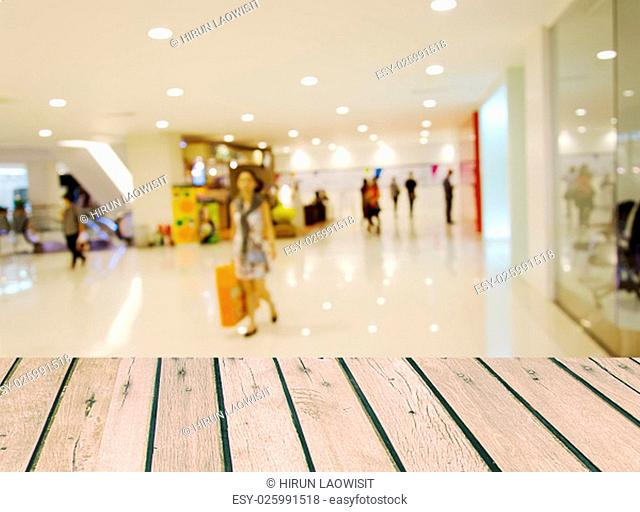 Wood table top and blurred shopping mall background. product display template.
