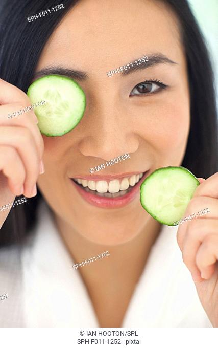 Mid adult woman holding cucumber slices, portrait