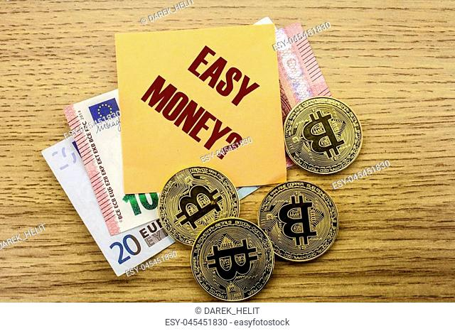Bitcoins, Bit Coin on Euro, Dollars notes witch sticky note on wooden background, EASY MONEY bitcoin concept