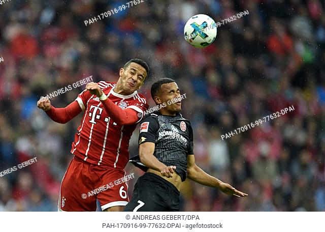 Thiago of Muenchen and Robin Quaison of Mainz vie for the ball during the German Bundesliga soccer match between Bayern Muenchen and FSV Mainz 05 in the Allianz...