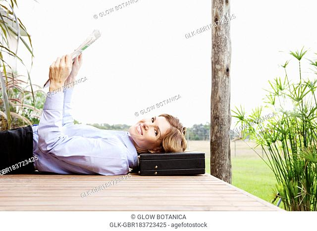 Businesswoman reading a newspaper in a park