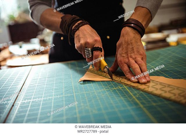 Mid-section of craftswoman cutting leather