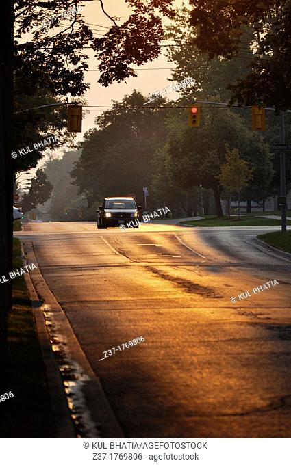 A car stops at a red light as the sun lights up the eastern sky at day break on a city street in Ontario, Canada