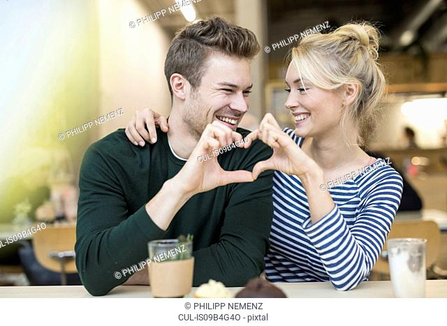 Couple making heart hands together in cafe