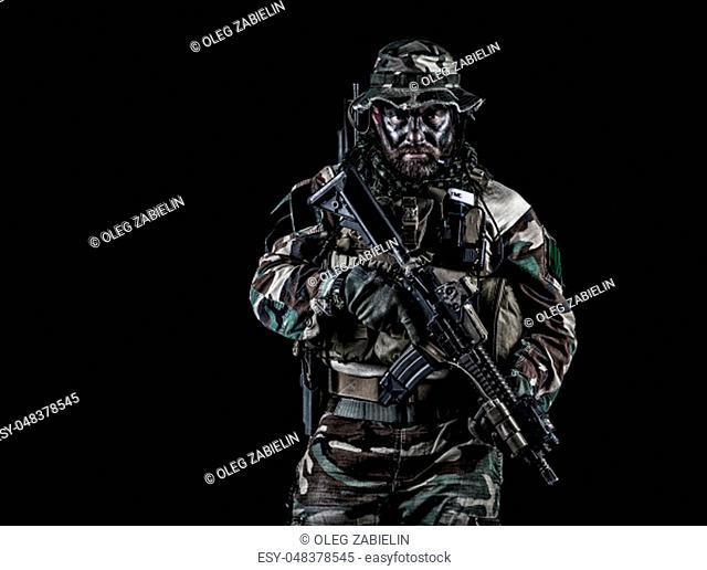Bearded Special forces United States in Camouflage Uniforms studio shot half length black background. Holding weapons, wearing jungle hat, Shemagh scarf
