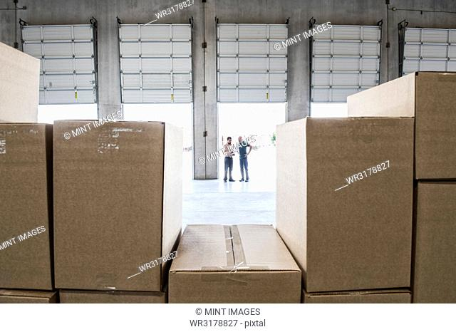 Team of workers check out inventory in front of loading dock doors in a new warehouse