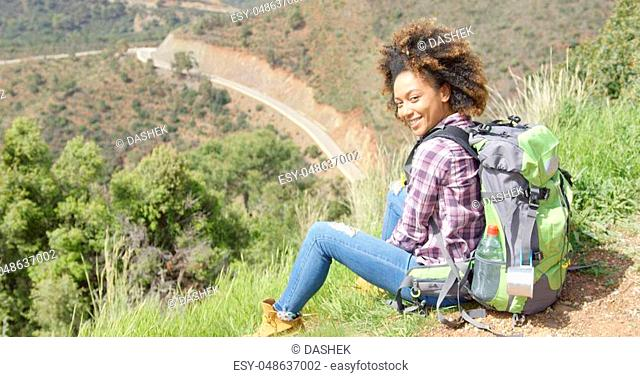 Young happy woman sitting with backpack on ground and looking at camera on background of summer mountains